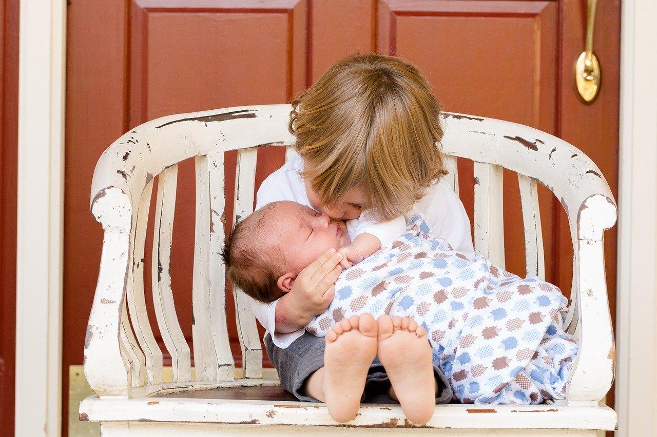 fetita tinand in brate fratele nou-nascut